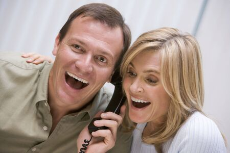 Couple receiving a good news phone call from clinic photo