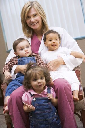 tots: Doctor sitting with three IVF children smiling Stock Photo