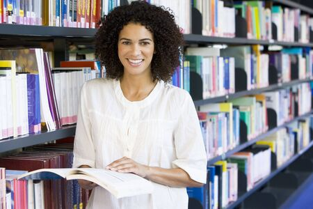Woman in library holding book (depth of field) Stock Photo - 3174789