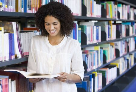 Woman in library reading book (depth of field) Stock Photo - 3174728