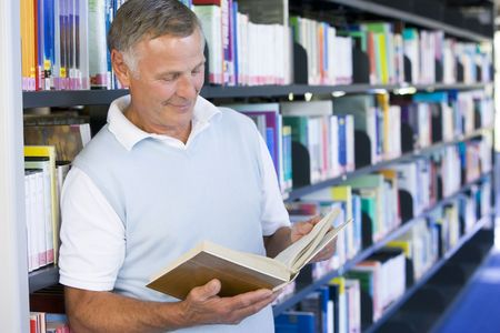 Man in library reading book (depth of field) photo