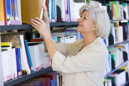 Woman in library pulling book off a shelf (depth of field) photo