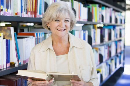 Woman in library holding book (depth of field) photo
