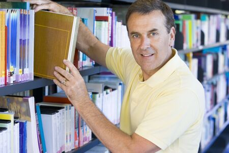 evening class: Man in library pulling book off a shelf (depth of field)
