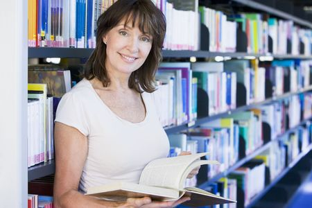 mature student: Woman in library holding book (depth of field)