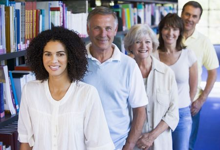 frontal views: Five people in library standing by bookshelves (depth of field)