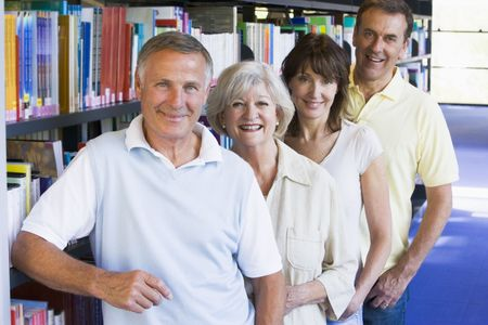 Four people in library standing by bookshelves photo
