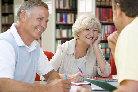 Tre persone in libreria iscritto nel notebook (attenzione selettiva)