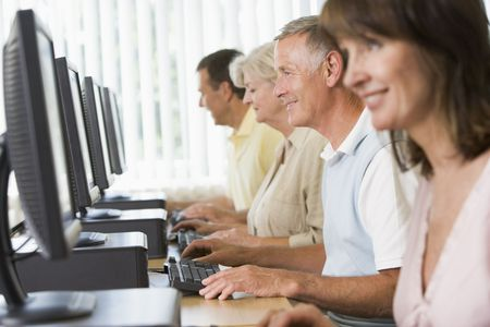 uses computer: Four people sitting at computer terminals (selective focushigh key)
