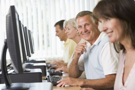 Four people sitting at computer terminals (selective focus/high key) Stock Photo - 3174196