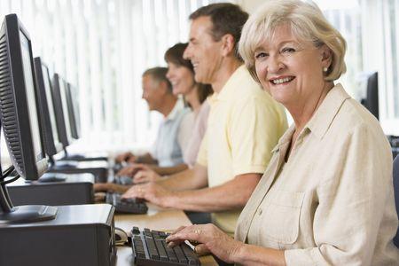 using the computer: Cuatro personas sentadas en terminales de computadora (profundidad de campo  clave de alta)