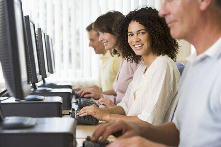 computer centres: Four people sitting at computer terminals (selective focushigh key)