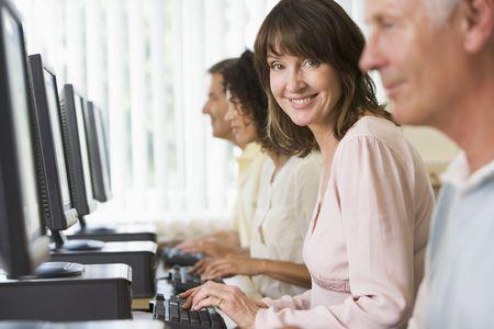 Cuatro personas sentadas en terminales de computadora (atención selectiva / alto clave)  Foto de archivo - 3174198