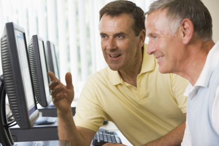 tutor: Dos hombres en una terminal de computadora hablar (profundidad de campo  clave de alta)  Foto de archivo