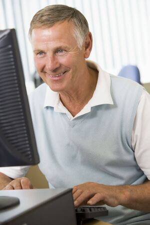 uses a computer: Man sitting at a computer terminal typing (high key)