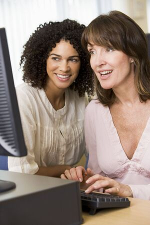 Two women at a computer terminal typing (high key) photo