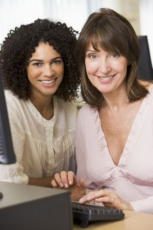 two friends: Two women at a computer terminal typing (high key)