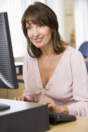 uses computer: Woman sitting at a computer terminal typing (high key)