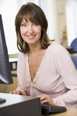 high key: Donna seduta a un computer terminale digitando (alta chiave)