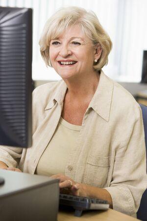 one senior adult woman: Mujer sentada en una terminal de computadora a escribir (clave de alta)
