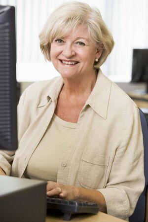 senior ordinateur: Femme assise � un terminal d'ordinateur de frappe (haute cl�)  Banque d'images