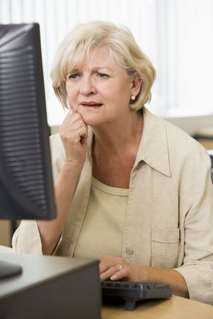 uses computer: Woman sitting at a computer terminal upset (high key)