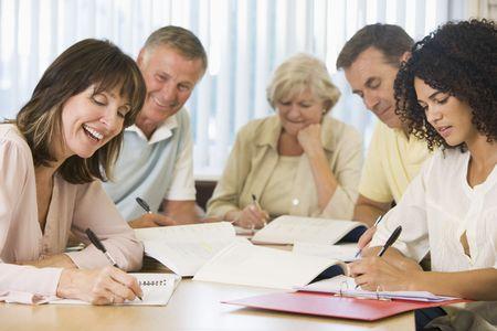 Cinco estudiantes adultos que estudian en la mesa (profundidad de campo)