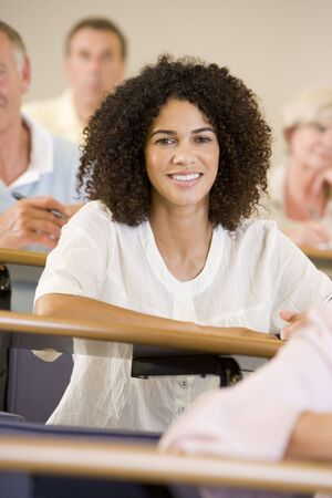 Woman sitting in adult classroom with students in background (selective focus) photo