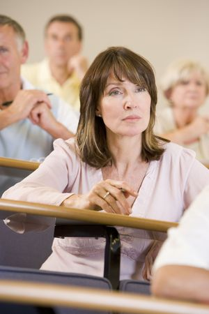 Woman sitting in adult classroom with students in background (selective focus) Stock Photo - 3173604