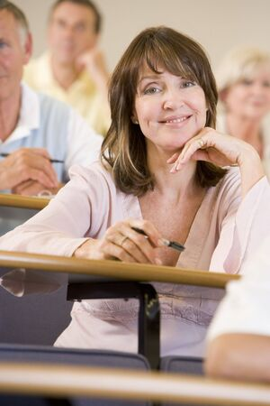 Woman sitting in adult classroom with students in background (selective focus) Stock Photo - 3174431