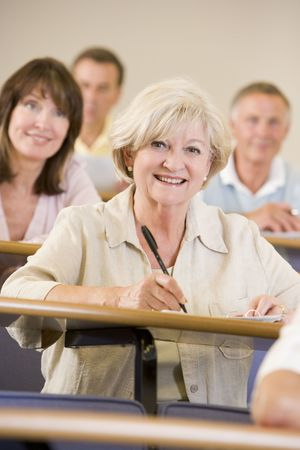 lecture theatre: Woman sitting in adult classroom with students in background (selective focus) Stock Photo