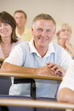 Man sitting in adult classroom with students in background (selective focus) Stock Photo - 3173654