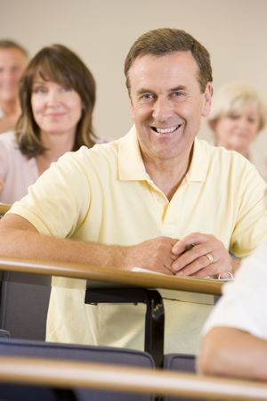 Man sitting in adult classroom with students in background (selective focus) photo