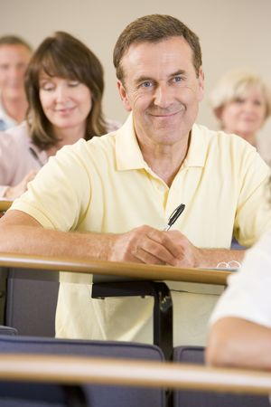 Man sitting in adult classroom with students in background (selective focus) Stock Photo - 3174386