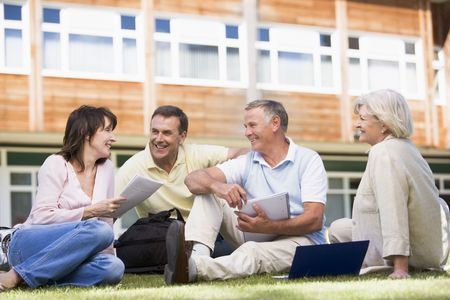 knap sack: Adult students on lawn of school studying and talking Stock Photo