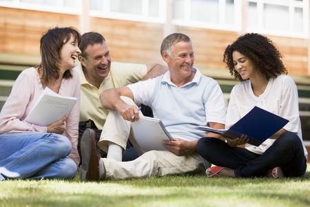 ruck sack: Adult students on lawn of school studying and talking Stock Photo
