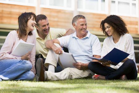 Estudiantes adultos en el césped de la escuela estudiando y hablando