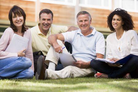 mature adult men: Studenti adulti a prato di scuola con i notebook