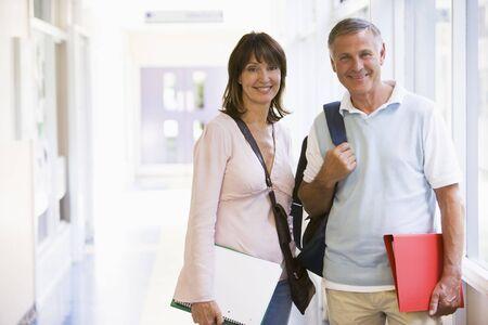 high key: L'uomo e la donna in piedi nel corridoio con libri (alta chiave)  Archivio Fotografico
