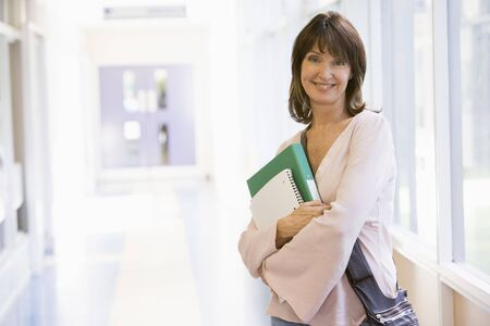 Woman standing in corridor with books (high key) Stock Photo - 3173514