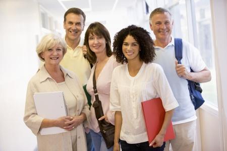 mature adult men: Cinque persone in piedi nel corridoio con libri (alta chiave)