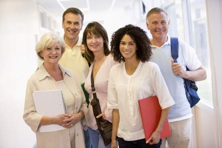 male senior adult: Five people standing in corridor with books (high key) Stock Photo