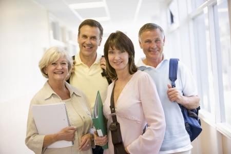 четыре человека: Four people standing in corridor with books (high key)