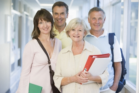 high key: Quattro persone in piedi nel corridoio con libri (alta chiave)  Archivio Fotografico