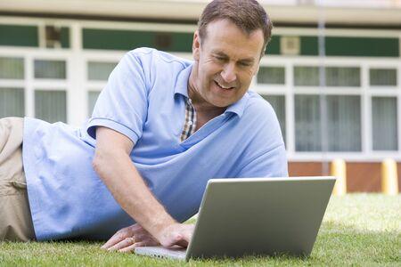 Man lying on lawn of school using laptop photo