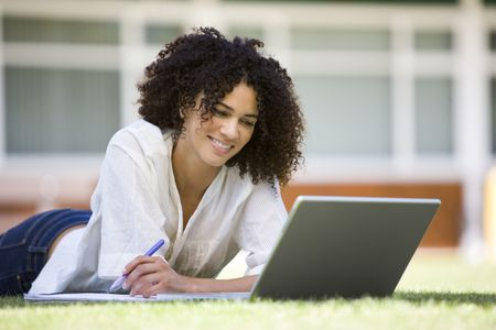 Woman lying on lawn of school with laptop Stock Photo - 3173609