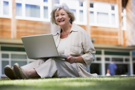 uses computer: Woman sitting on lawn of school with laptop Stock Photo