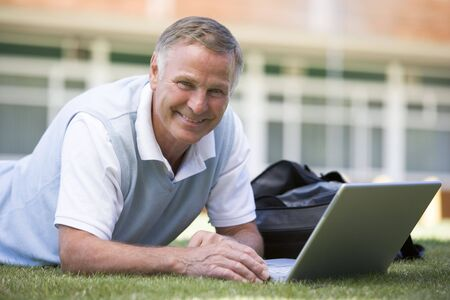 Man lying on lawn of school with laptop photo