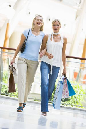 looking towards camera: Two women at a shopping mall