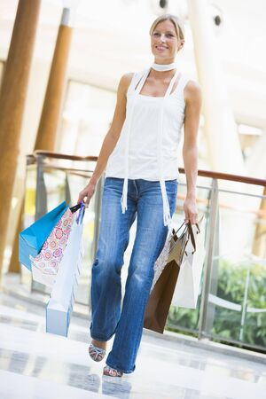one mid adult woman only: Woman with shopping bags at a shopping mall Stock Photo
